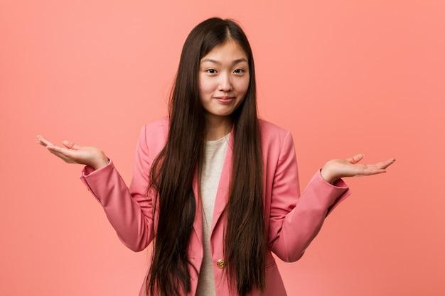 ジェスチャの質問で肩を疑って肩をすくめてピンクのスーツを着ている若いビジネス中国の女性