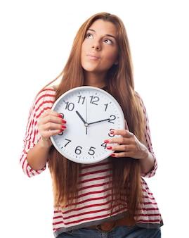 Задумчивый женщина, держащая часы