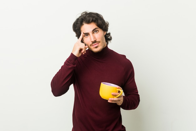 Молодой человек, держа чашку кофе, указывая пальцем на висок, думая, сосредоточены на задаче