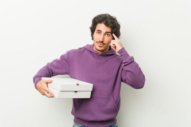 指で彼の寺院を指しているピザのパッケージを保持している若い男、思考、タスクに焦点を当てた