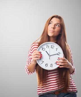 Женщина, держащая часы мышления