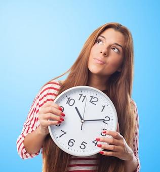 Красивая женщина, глядя вверх держит часы