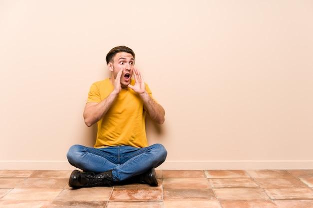 床に座っている若い男が大声で叫ぶ、目を開いたまま、緊張した手