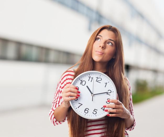 Женщина, глядя вверх проведение часы