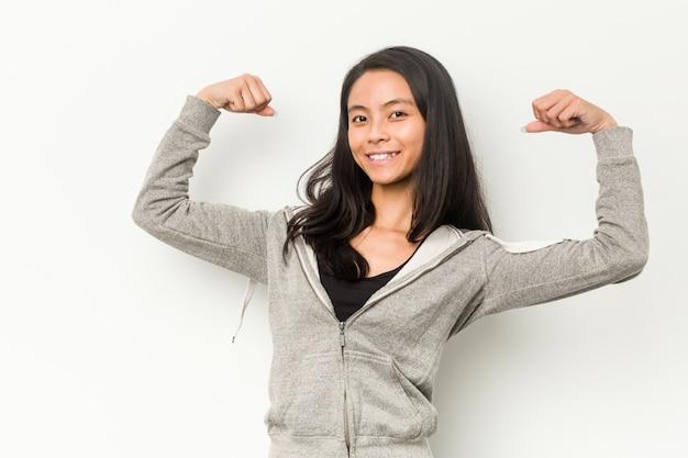 腕、女性の力の象徴と強度ジェスチャーを示す若いフィットネス中国の女性