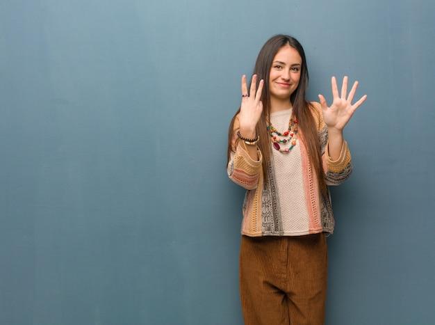 Молодая женщина хиппи показывает номер восемь