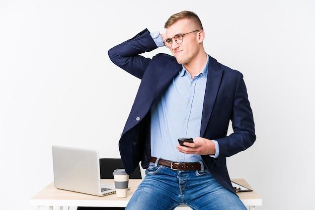 頭の後ろに触れる、思考と選択を行うラップトップを持つ若いビジネスマン