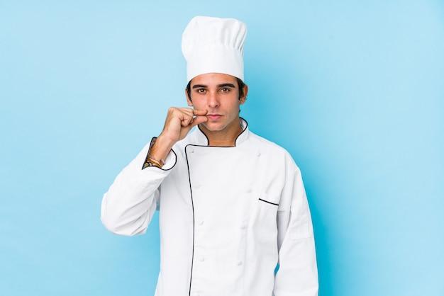 秘密を保つ唇に指で分離された若い料理人。