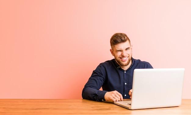 Молодой человек работает с его ноутбуком, подмигивая, веселый, дружелюбный и беззаботный.