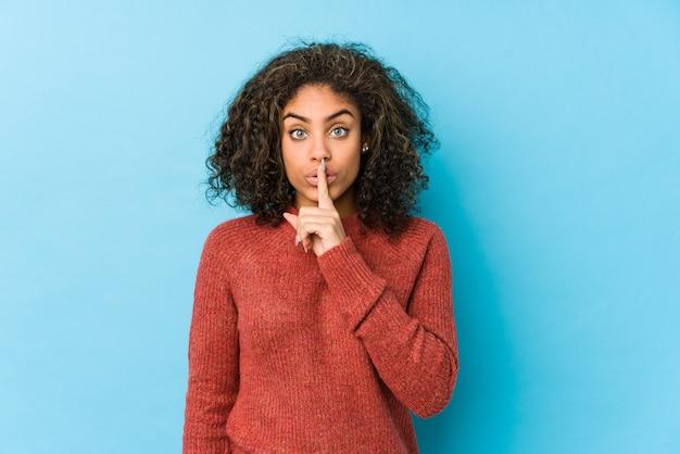 若いアフリカ系アメリカ人の巻き毛の女性が秘密を守るか沈黙を求めています。