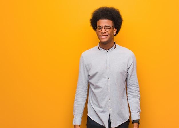 Молодой человек за оранжевой стеной подмигивает, веселый, дружелюбный и беззаботный жест