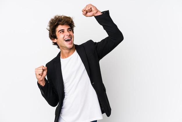 Молодой человек поднимает кулак после победы