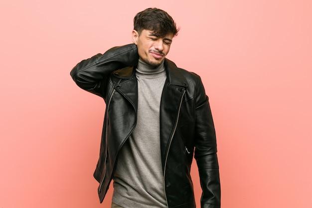 Молодой латиноамериканский человек, носящий кожаную куртку, страдающую болью шеи из-за сидячего образа жизни.