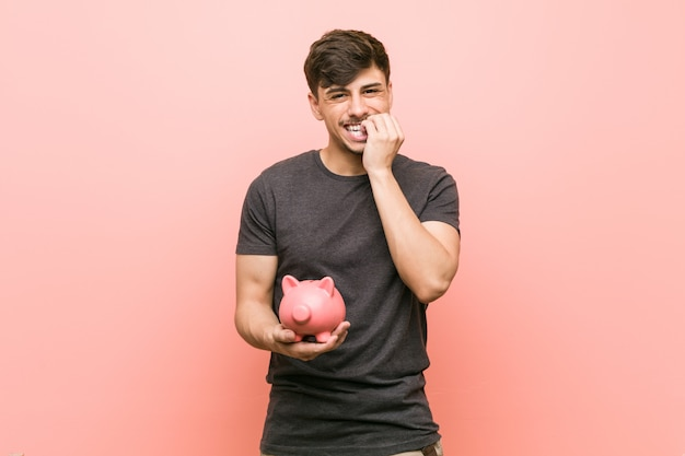 Молодой латиноамериканский человек, держащий копилку, кусающий ногти, нервный и очень взволнованный.