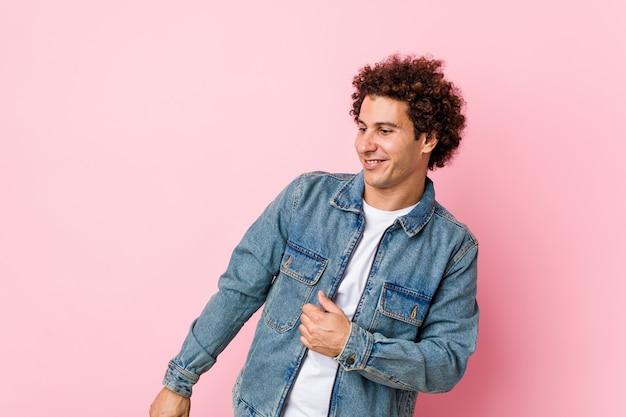 ピンクの壁ダンスと楽しんでデニムジャケットを着て巻き毛の成熟した男。