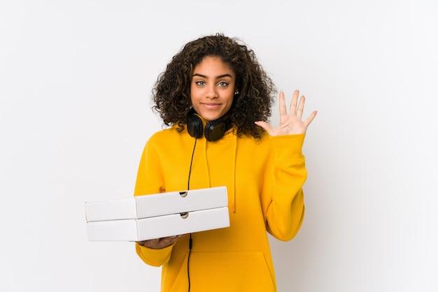 Молодой студент женщина, держащая пиццы, улыбаясь веселый показ номер пять с пальцами