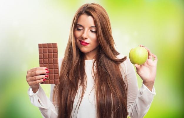 Женщина, выбирая между пищевыми продуктами