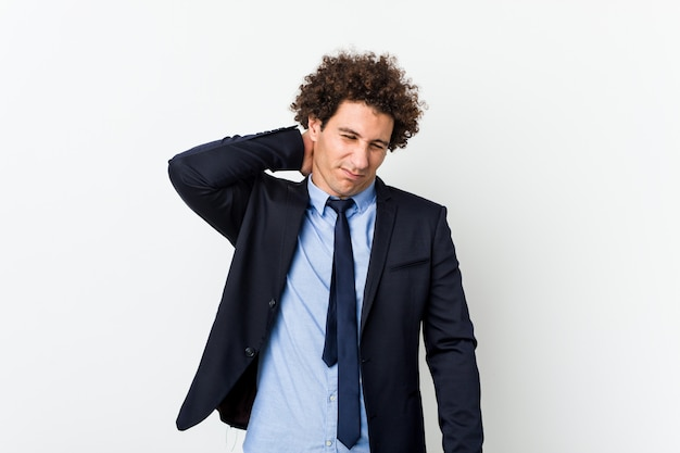Молодой бизнес кудрявый мужчина страдает от боли в шее из-за малоподвижного образа жизни