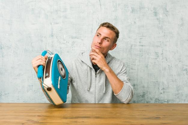 Молодой человек слушает радио, глядя в сторону с сомнительным и скептическим выражением