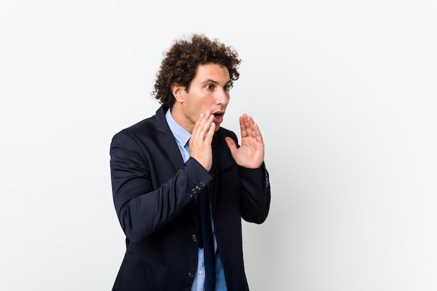 Молодой бизнес кудрявый человек против белой стене громко кричит, держит глаза открытыми и руки напряженными.