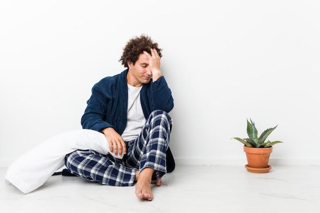 Зрелый человек в пижаме сидит на полу дома, забывая что-то, хлопая по лбу ладонью и закрывая глаза.