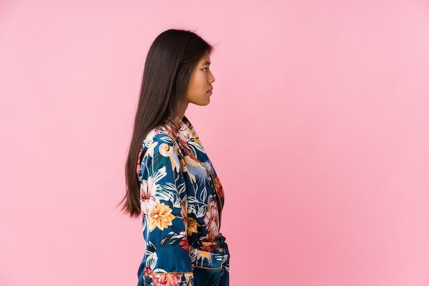 左を見つめる着物パジャマを着た若いアジア女性、横向きのポーズ。