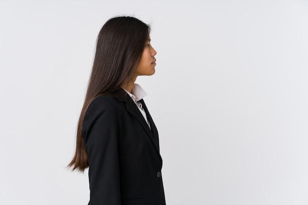 Молодая азиатская бизнес-леди смотря налево
