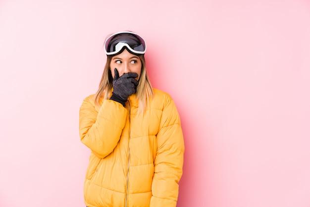 思慮深い探していると手で口を覆っているスキー服を着た若い女性
