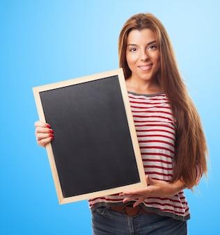 手の中に小さな黒板を保持している学生の女の子