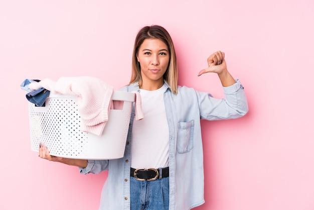 Молодая кавказская женщина, собирающая грязную одежду, чувствует себя гордой и уверенной в себе, примером для подражания.