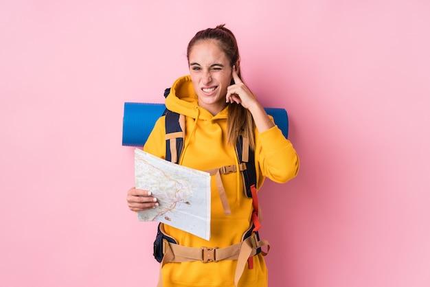若い旅行者の白人女性は、手で耳を覆って分離しました。