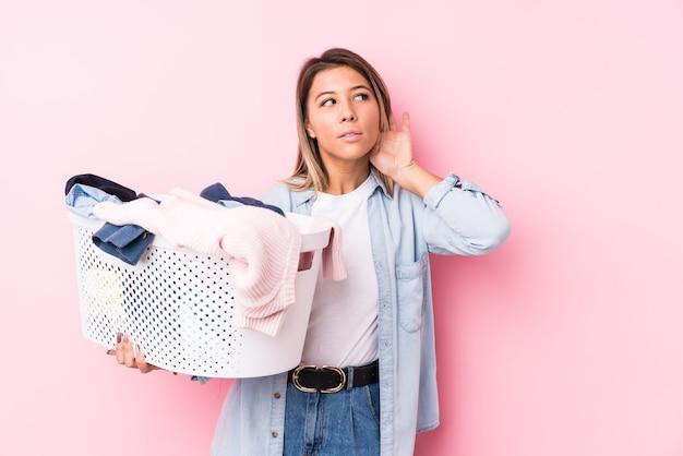 Молодая женщина, собирание грязную одежду, пытаясь слушать сплетни