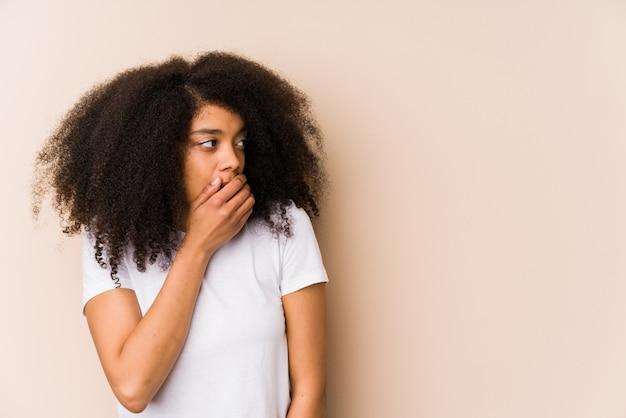 思慮深い探していると手で口を覆っている若い女性