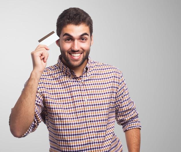プラスチックカードを示す歯を見せる笑顔の男。