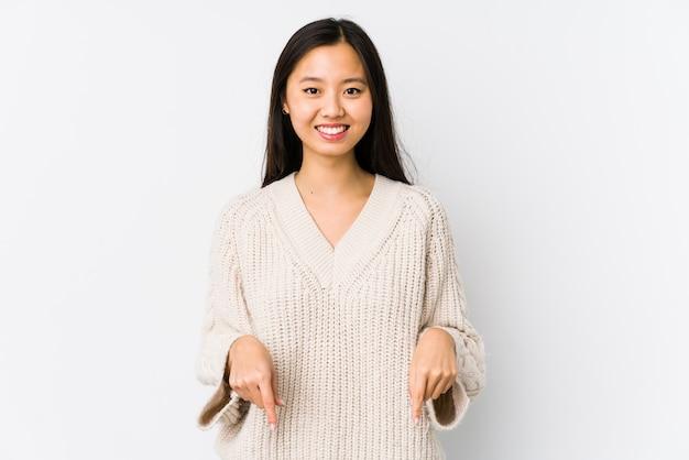 Молодая азиатская женщина указывает пальцами вниз