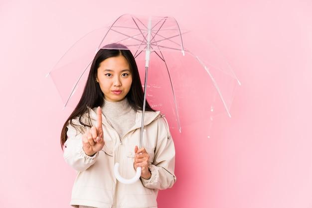 指でナンバーワンを示す傘を保持している若いアジア女性