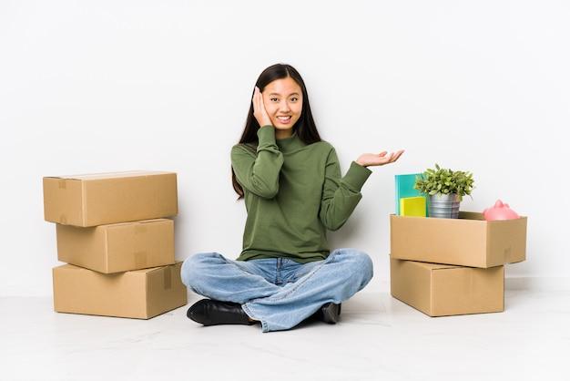 新しい家に移動する若いアジア女性は手のひらに何かを保持し、頬に手を保持します