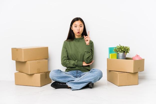 いくつかの素晴らしいアイデアを持つ新しい家に移動する若いアジア女性