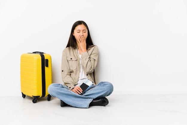 搭乗を持って座っている若いアジア旅行者の女性は、手で口を覆っている疲れたジェスチャーを示すあくびを渡します