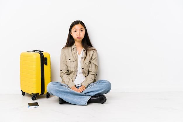 搭乗券を持って座っている若いアジア旅行者の女性が頬を吹く、疲れた表情