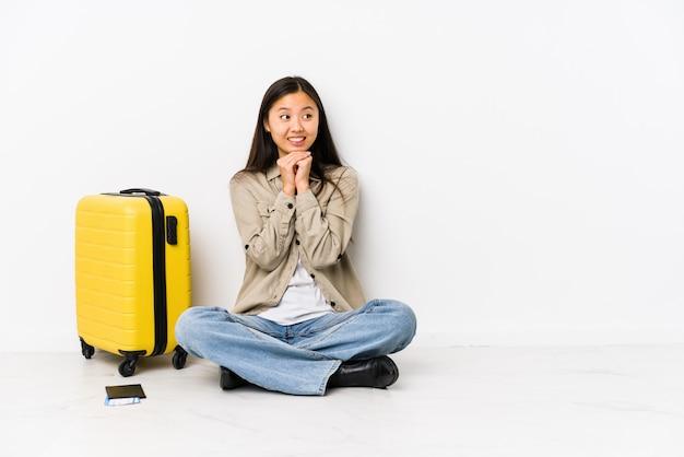搭乗券を持って座っている若いアジア旅行者の女性は、あごの下で手をつないで、喜んで脇を探しています