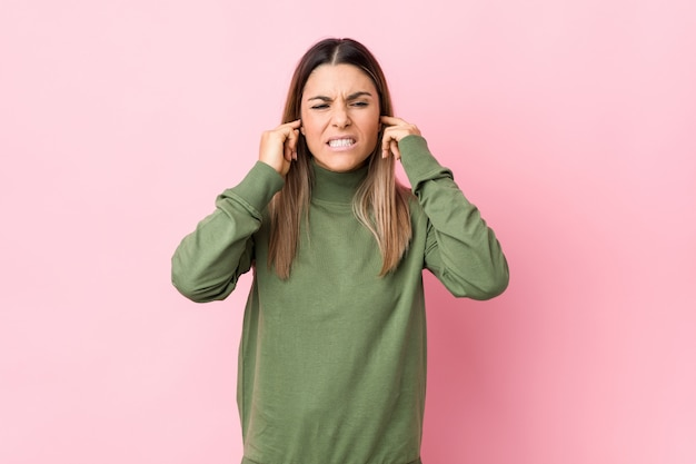 若い女性の手で耳を覆う