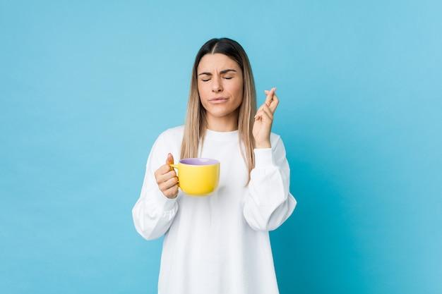 Молодая женщина, держащая чашку кофе скрещивание пальцев для удачи