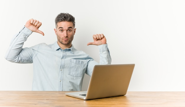 彼のラップトップで働く若いハンサムな男は、誇りに思って、自信を持って、次の例です。