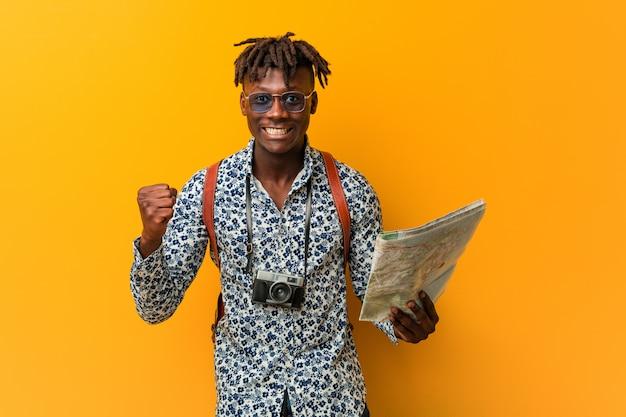 Молодой раста черный человек держит карту аплодисменты беззаботной и взволнован. концепция победы.