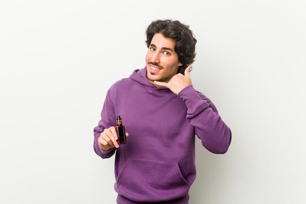 指で携帯電話呼び出しジェスチャーを示す気化器を保持している若い男。