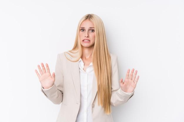 Женщина молодого дела белокурая на белой стене отвергая кто-то показывая жест отвращения.