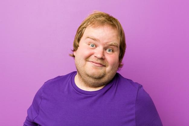 Молодой подлинный рыжий толстый человек, показывая желанное выражение.