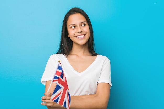 Молодая испанская женщина держит флаг соединенного королевства, улыбаясь уверенно со скрещенными руками.