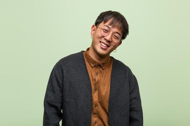 緑の壁に対してクールな服のスタイルを着ている若い中国人男性